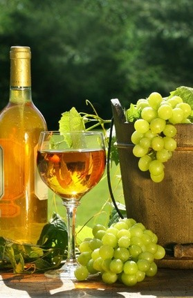 White wine with bottle and grapes on a rustic table