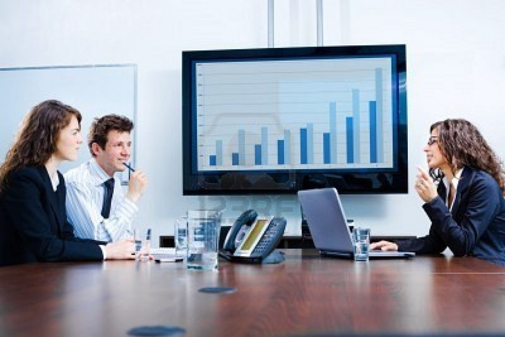 4107030-happy-young-businesspeople-having-meeting-in-boardroom-at-office-in-front-of-a-huge-plasma-tv-screen